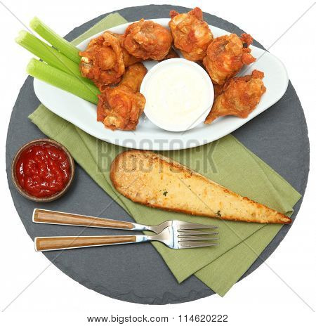 Spicy Chicken Wings with Celery Sticks and Ranch top view on slate over white.