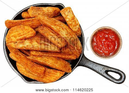 Baked Seasoned Potato Wedges in Cast Iron Skillet With Ketchup Isolated over white.