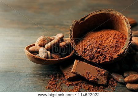Bowl with cocoa powder and chocolate on wooden background, close up