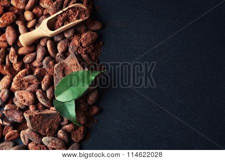 Aromatic cocoa beans and chocolate on grey background, copy space
