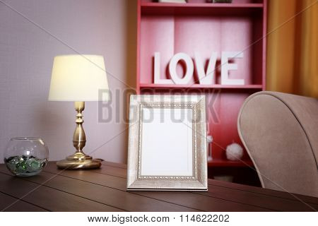 Frame on wooden table in the room against red bookcase