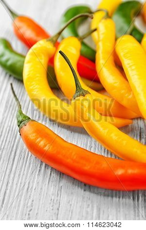 Yellow chili peppers on light wooden background