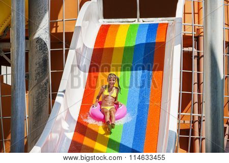 Child girl on water slide at aquapark.