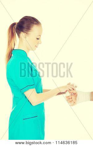 Woman doctor bandaging female hand.