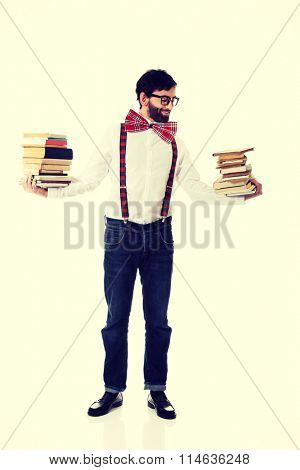 Man wearing suspenders with stack of books.