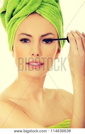 Woman with turban applying make up.