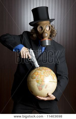 Man in gas mask holding a gun to an earth globe