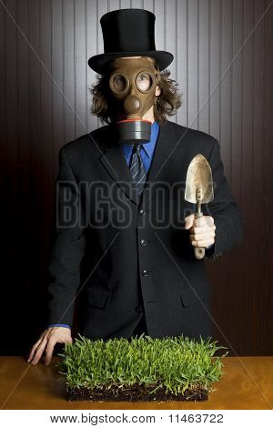 man in gas mask holding a potting shovel standing over a patch of grass