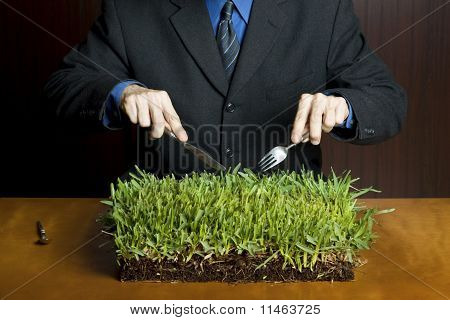 man holding a fork and knife over a patch of grass