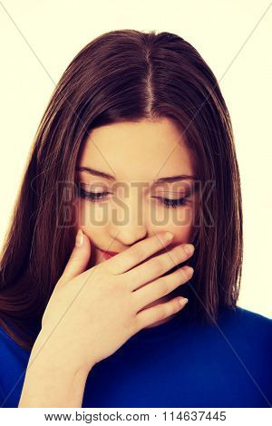 Disgusted teen covering her mouth.