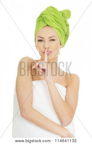 Woman with turban towel make hush gesture.