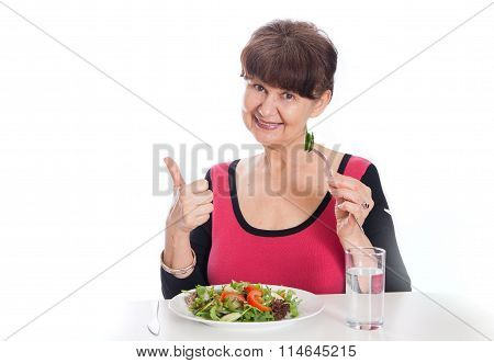 Elderly good looking woman eating green salad. Healthy life style concept