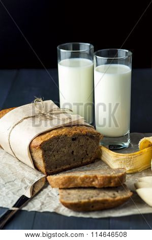 Banana bread with glasses of milk on baking paper