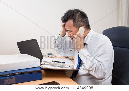Stressful And Frustrated Asian Manager Talking On Telephone In Office