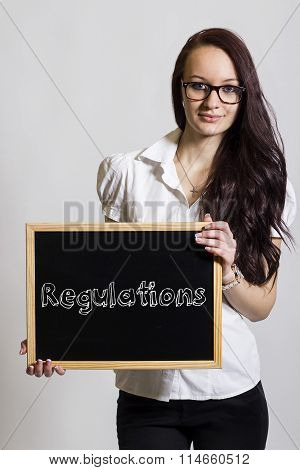 Regulations - Young Businesswoman Holding Chalkboard