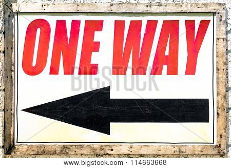 Vintage One Way Sign With Black Arrow Showing The Direction Under Red Letters