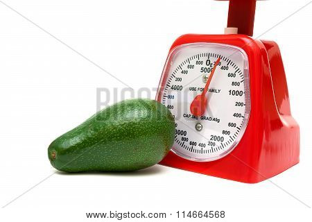 Ripe Avocado And Kitchen Scales On A White Background