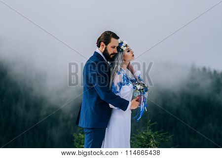Groom In A Blue Suit And Bride In White In The Mountains Carpathians