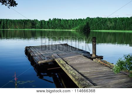 Old wooden pier on a lake at sunrise