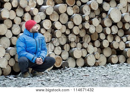 Hunkering worker having a rest at pile of logged firewood background outdoors in winter mountain for