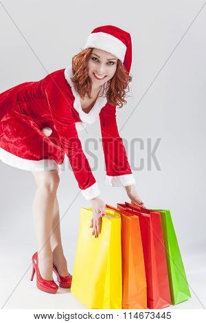 Happy Smiling Caucasian Ginger Santa Helper Girl With Colorful Shopping Bags