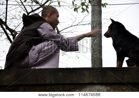 Buddhist Monk Playing With A Stray Dog