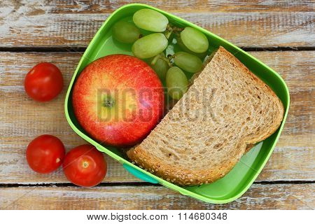 Lunch box consisting of wholegrain sandwich, apple, grapes and cherry tomatoes