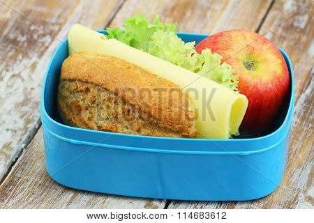 Packed school lunch box containing brown cheese roll and red apple