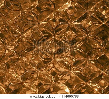 Gold glass texture with a pattern of rhombuses. Clear glass diamond shape. Crystals. Closeup