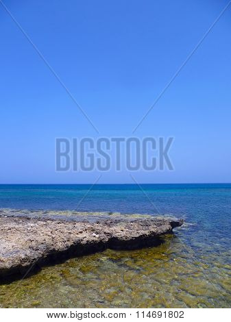 Rocky coast stretching into the distance beyond the horizon of the blue ocean against a pure, cloudl