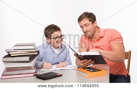 Boy doing homework together with his father
