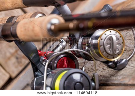 Closeup Fishing Reel On Wooden Board Background