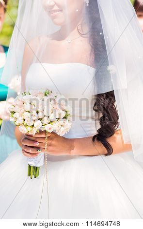 Serious young bride in veil holding bouquet