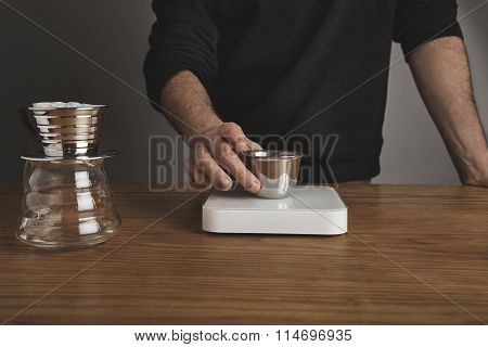 Barista Holds Cup With Ground Coffee Above Weights