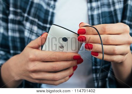 Girl In Plaid Shirt Holding A Smart Phone In Her Hands With Red Manicure And Connects Headphones