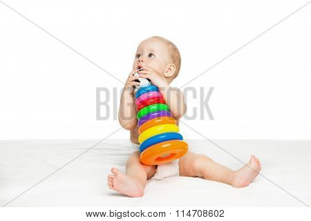 cute baby sitting and playing with colorful toy