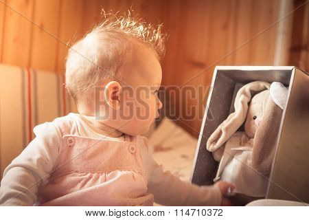 Baby girl playing with plush rabbit received as a gift