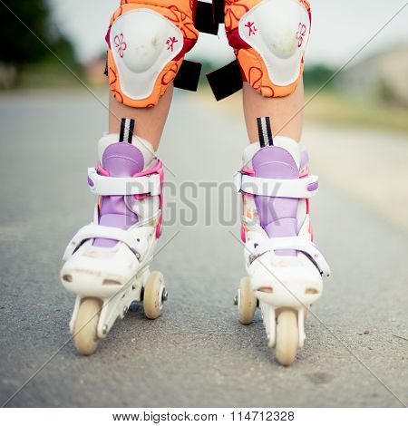 Legs of a child riding roller skates with protection pads on knees