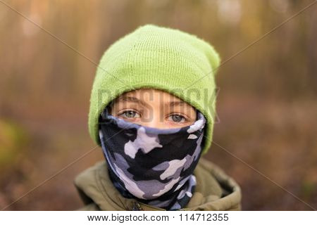 Young boy wearing a hat and bandanna covering his face