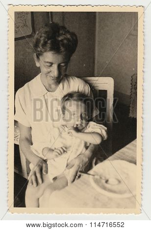 A small boy with mother during the meal  - vintage photo