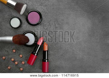 Make-up brush, lipsticks, eye-shadow and blusher, on grey background