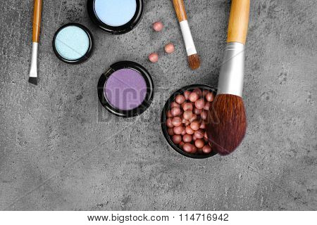 Make-up brushes, eye-shadow and blusher, on grey background