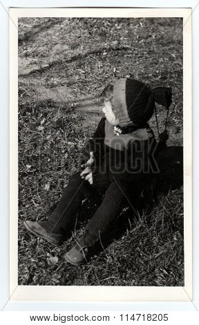 Vintage photo shows a small child sits on grass