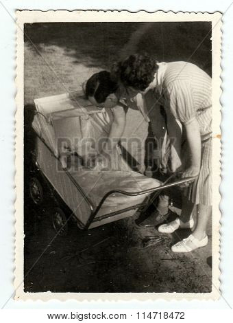Vintage photo shows baby girl in a pram (baby carriage) with parents
