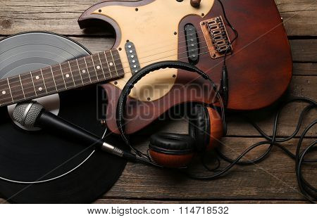 Electric guitar and headphones with microphone and vinyl on wooden background