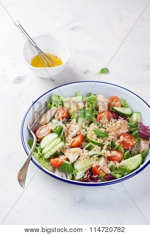 Salad with chicken, vegetables, bulgur and olive oil in an enamel plate.