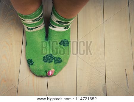 worn out socks with a hole and toes sticking out of them on old wooden floor.