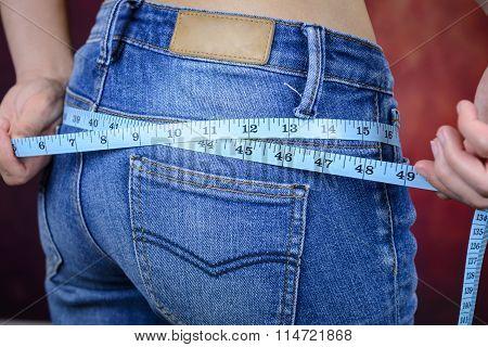 Slim Woman Measuring Body, Wearing Jeans