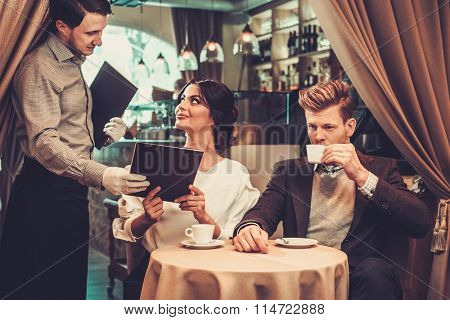 Waiter taking order from stylish wealthy couple in restaurant.