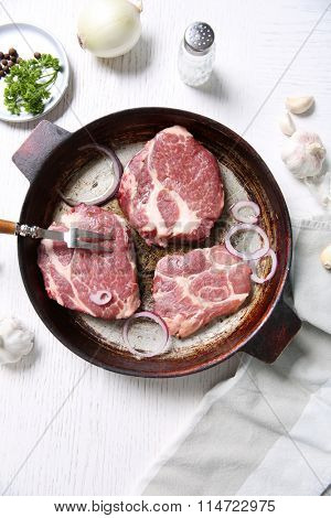 Marbled beef steak on pan and spices on color wooden background